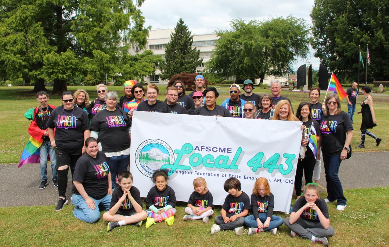 WFSE Local 443 members and their families hold a banner and pose during the Olympia Pride parade.